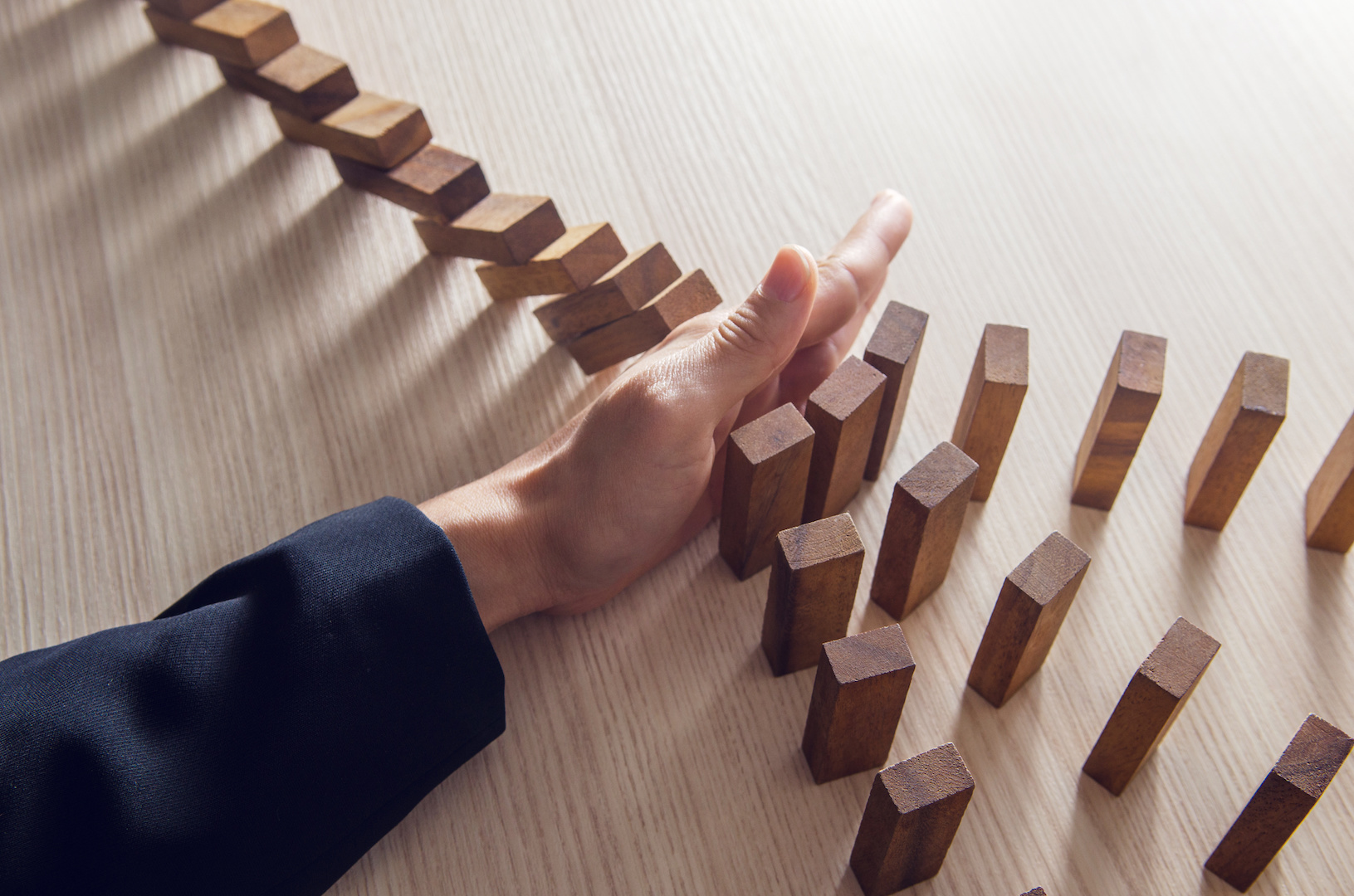 Domino Effect. Businesswoman hand stopping the domino wooden effect concept for business.